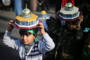 Palestinian children hold models depicting the Dome of the Rock during a protest near the central Gaza Strip