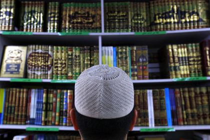 "Man wearing an Islamic prayer cap, or ""Kufi"", looks at Islamic books on display at a bookshop located in the western Sydney suburb of Lakemba"