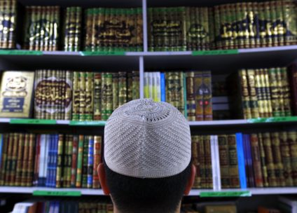 """Man wearing an Islamic prayer cap, or """"Kufi"""", looks at Islamic books on display at a bookshop located in the western Sydney suburb of Lakemba"""