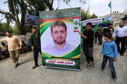 Palestinian men hold up a poster portrait of 35-year-old Palestinian professor and Hamas member Fadi Mohammad al-Batsh who was killed early in the day in Malaysia outside his family's house in Jabalia in the northern Gaza strip