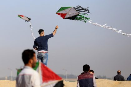 A Palestinian youth flies a kite during a tent city protest along Israel border with Gaza, demanding to return to their home land, east of Gaza City