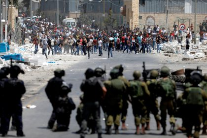 Palestinian protesters hurl stones at Israeli troops in the West Bank village of Beita near Nablus