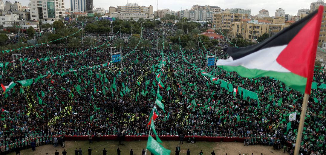 Palestinian flag flies as Hamas supporters take part in a rally marking the 30th anniversary of Hamas' founding, in Gaza City