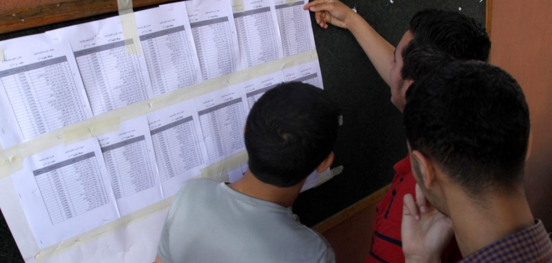 """Palestinian students look for their names in the final high school exams, known as """"Tawjihi"""""""