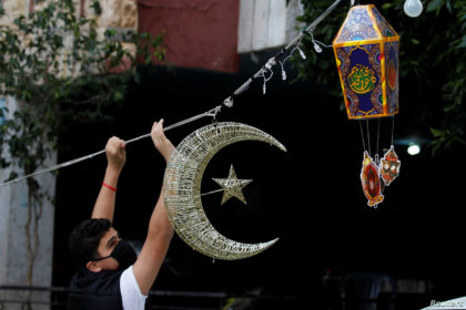 A man puts Ramadan decorations on a street ahead of the Muslim holy month of Ramadan, during a countrywide lockdown over the coronavirus disease (COVID-19) in Beirut