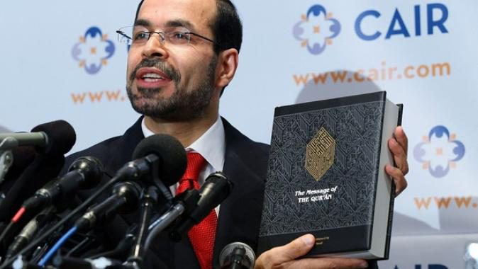 National-Executive-Director-of-Council-on-American_Islamic-RelationsCAIR-Nihad-Awad-holds-a-translated-copy-of-the-Quran-as-he-speaks-news-conference-at-the-headquarters-of-CAIR